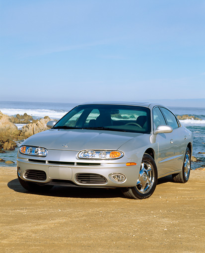 AUT 34 RK0035 04 © Kimball Stock 2001 Oldsmobile Aurora V8 Silver 3/4 Front View On Sand Ocean Blue Sky