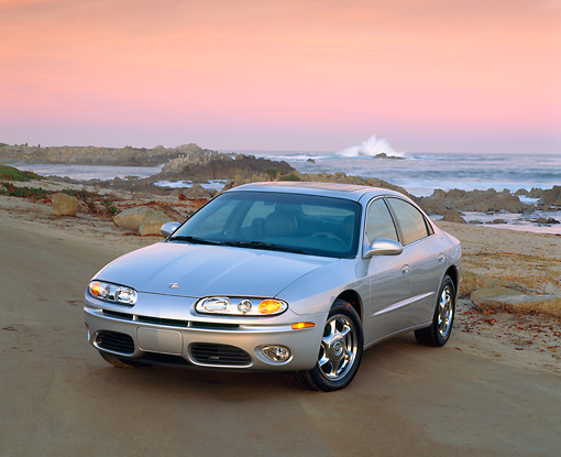 AUT 34 RK0041 01 © Kimball Stock 2001 Oldsmobile Aurora V8 Silver 3/4 Front View On Sand By Ocean At Dusk