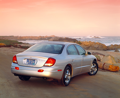 AUT 34 RK0044 03 © Kimball Stock 2001 Oldsmobile Aurora V8 Silver 3/4 Rear View On Pavement By Ocean Filtered
