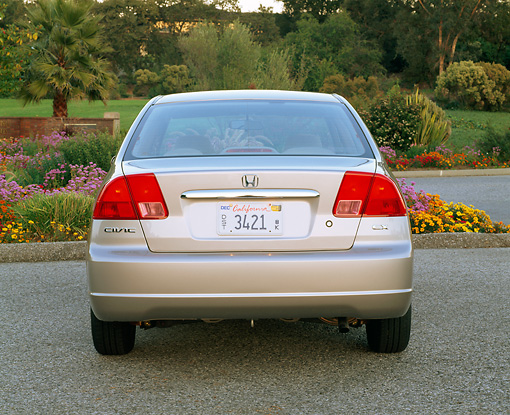 AUT 34 RK0142 02 © Kimball Stock 2001 Honda Civic EX Champagne Rear Shot On Pavement By Flowers And Trees