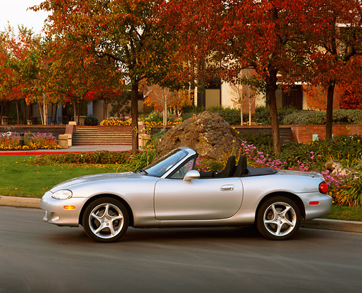 AUT 34 RK0160 05 © Kimball Stock 2001 Mazda Miata Convertible Silver Profile View On Pavement By Trees