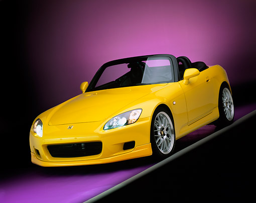 AUT 34 RK0339 02 © Kimball Stock 2001 Honda S2000 Convertible Yellow 3/4 Front View On Gray Line Purple Floor And Lighting Studio