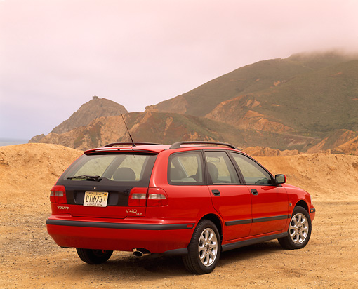 AUT 34 RK0009 02 © Kimball Stock 2001 Volvo V40 Red 3/4 Rear View On Sand Overcast By Hills