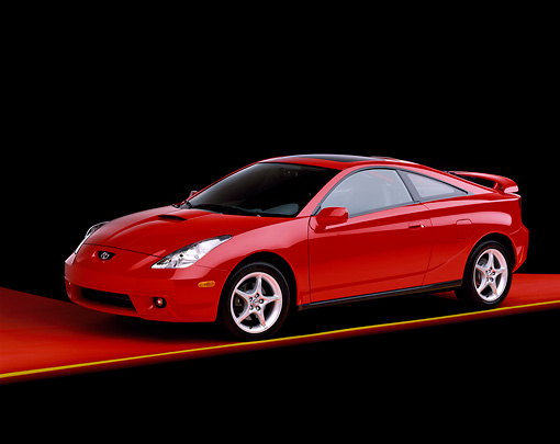 AUT 34 RK0028 02 © Kimball Stock 2001 Toyota Celica Red 3/4 Side View On Red Floor Yellow Line Studio