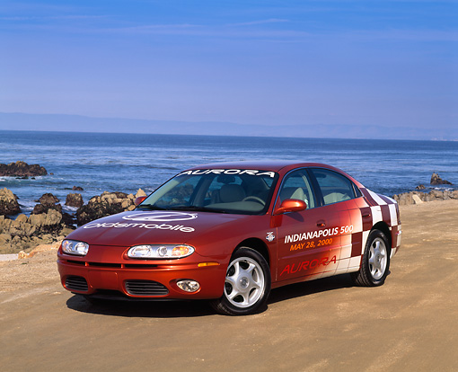 AUT 34 RK0045 01 © Kimball Stock 2001 Oldsmobile Aurora Indy 500 Pace Car 3/4 Front View On Sand By Ocean Blue Sky