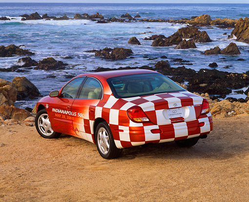 AUT 34 RK0047 01 © Kimball Stock 2001 Oldsmobile Aurora Indy 500 Pace Car 3/4 Rear View On Sand By Ocean