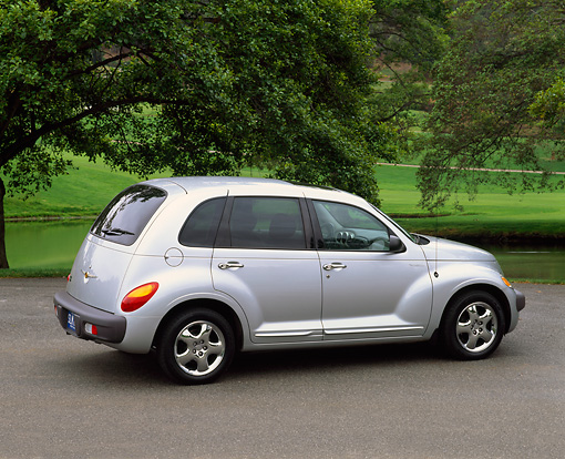 AUT 34 RK0060 03 © Kimball Stock 2001 Chrysler PT Cruiser Silver 3/4 Rear View On Pavement By Trees