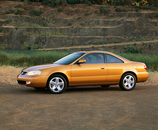 AUT 34 RK0076 01 © Kimball Stock 2001 Acura 3.2CL Gold 3/4 Side View On Dirt By Water Against Rock Mountain