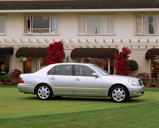 AUT 34 RK0105 03 © Kimball Stock 2001 Lexus LS430 Silver 3/4 Front View On Grass By Building