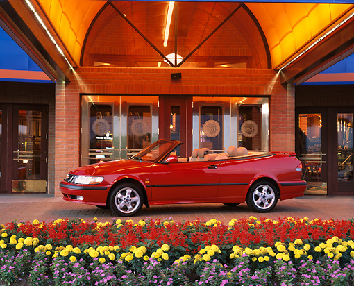AUT 34 RK0109 06 © Kimball Stock 2001 Saab 9-3 Convertible Red 3/4 Side View In Front Of Entrance By Flowers
