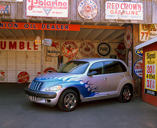 AUT 34 RK0133 03 © Kimball Stock 2001 Chrysler PT Cruiser Silver Blue Flames 3/4 Side View On Pavement In Garage