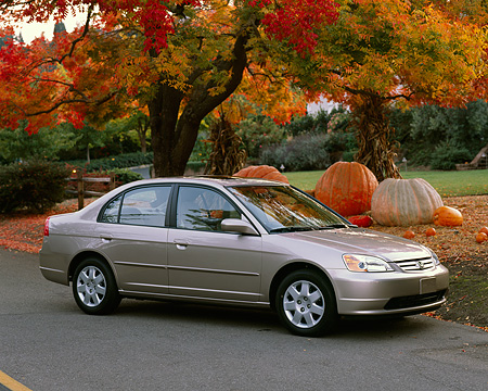 AUT 34 RK0138 01 © Kimball Stock 2001 Honda Civic EX Champagne 3/4 Side View On Pavement By Pumpkins And Fall Colored Trees