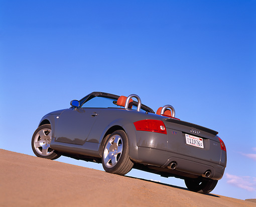 AUT 34 RK0149 01 © Kimball Stock 2001 Audi TT Roadster Gray Slanted 3/4 Rear View On Pavement Hill Blue Sky