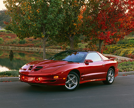 AUT 34 RK0172 05 © Kimball Stock 2001 Pontiac Firebird Trans Am Sunset Orange 3/4 Front View On Pavement By Water   And Fall Trees