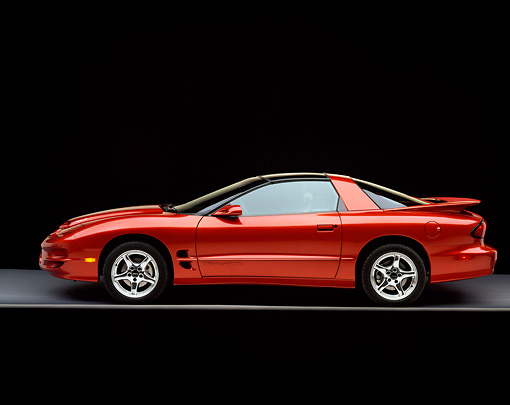 AUT 34 RK0175 06 © Kimball Stock 2001 Pontiac Firebird Trans Am Sunset Orange Profile View On Gray Floor Studio