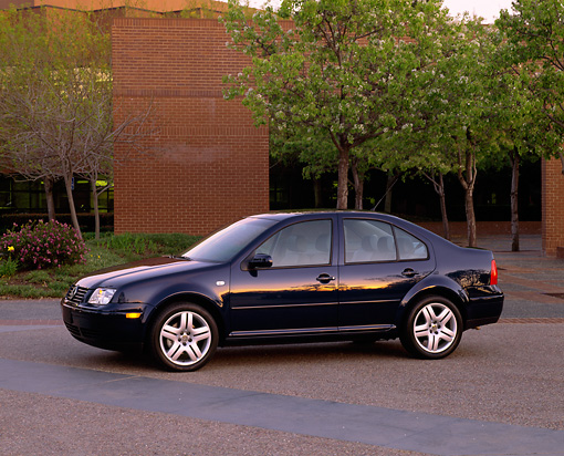 AUT 34 RK0264 02 © Kimball Stock 2001 VW Jetta GLS 1.8T Blue Side 3/4 View On By Building And Trees