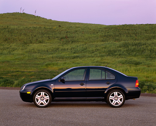 AUT 34 RK0268 03 © Kimball Stock 2001 Volkswagen Jetta GLS 1.8T Blue Profile View On Pavement By Grass Hills At Dusk