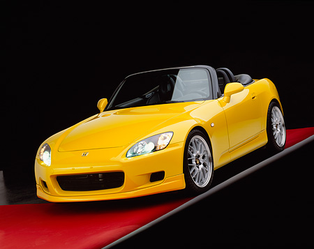 AUT 34 RK0338 02 © Kimball Stock 2001 Honda S2000 Convertible Yellow 3/4 Front View On Gray Line Red Floor Studio