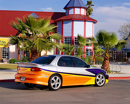 AUT 34 RK0360 02 © Kimball Stock 2001 Chevrolet Cavalier Yellow And Silver 3/4 Rear View On Pavement By Building Pal Tree