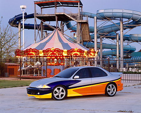 AUT 34 RK0361 01 © Kimball Stock 2001 Chevrolet Cavalier Silver And Yellow Front 3/4 View On Pavement By Amusement Park