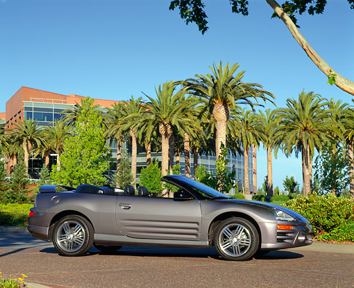 AUT 35 RK0219 03 © Kimball Stock 2002 Mitsubishi Eclipse GTS Spyder Gray Low 3/4 Side View By Palm Trees And Building