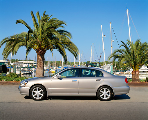 AUT 35 RK0241 04 © Kimball Stock 2002 Infiniti Q45 Luxury Sedan Silver Profile View On Pavement By Harbor