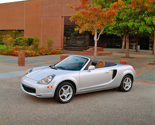 AUT 35 RK0273 01 © Kimball Stock 2002 Toyota MR2 Convertible Silver 3/4 Side View On Pavement By Building