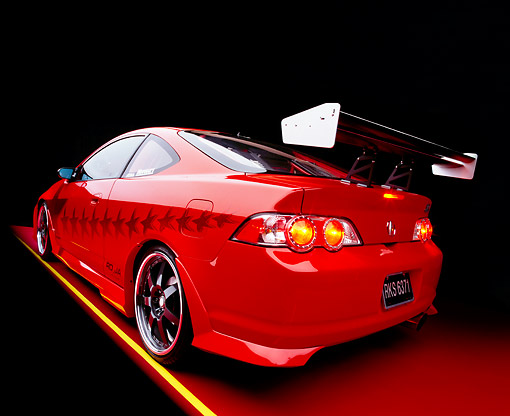 AUT 35 RK0343 06 © Kimball Stock 2002 Acura RSX Type S Red With Graphics Modify By APC Wide Angle 3/4 Rear Side View On Red Floor Studio