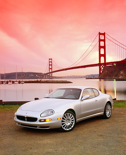 AUT 35 RK0356 05 © Kimball Stock 2002 Maserati GT Coupe Silver 3/4 Front View On Dirt By SF Bridge Filtered