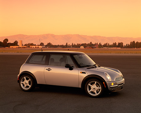 AUT 35 RK0052 01 © Kimball Stock 2002 BMW Mini Cooper Silver Side 3/4 View On Pavement Mountains Yellow Sky