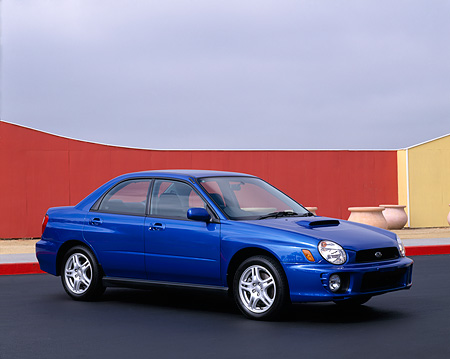 AUT 35 RK0060 01 © Kimball Stock 2002 Subaru WRX Impreza Blue Front 3/4 View On Pavement By Red Fence