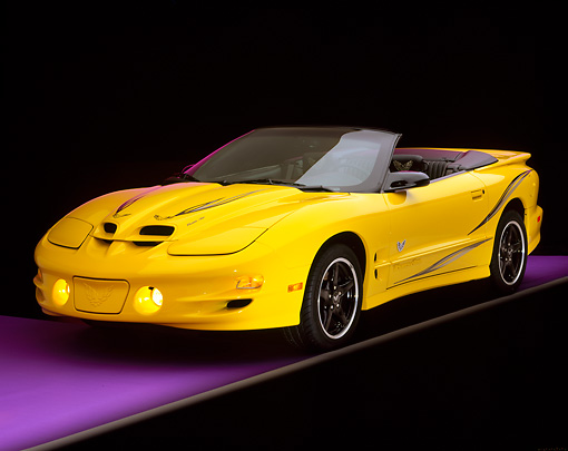 AUT 35 RK0065 02 © Kimball Stock 2002 Pontiac Firebird Trans Am Convertible Yellow 3/4 Front View On Purple Floor Gray Line Studio