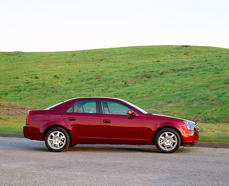 AUT 35 RK0119 02 © Kimball Stock 2002 Cadillac CTS Burgundy Profile On Pavement By Grass Hill