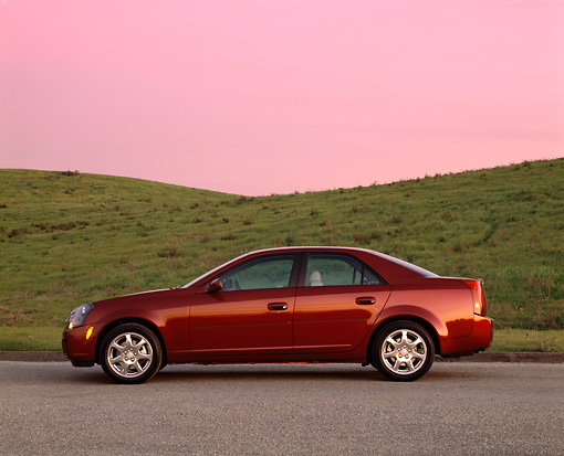 AUT 35 RK0120 02 © Kimball Stock 2002 Cadillac CTS Burgundy Profile View On Pavement Grass Hills Filtered
