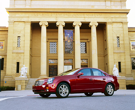 AUT 35 RK0121 03 © Kimball Stock 2002 Cadillac CTS Burgundy Low 3/4 Side View On Pavement By Building
