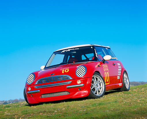 AUT 35 RK0133 05 © Kimball Stock 2002 Mini Mania Mini Cooper Red Slanted 3/4 Front View On Grass Hill
