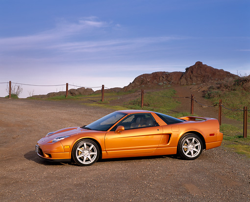 AUT 35 RK0149 02 © Kimball Stock 2002 Acura NSX Imola Orange 3/4 Front View On Dirt Blue Sky