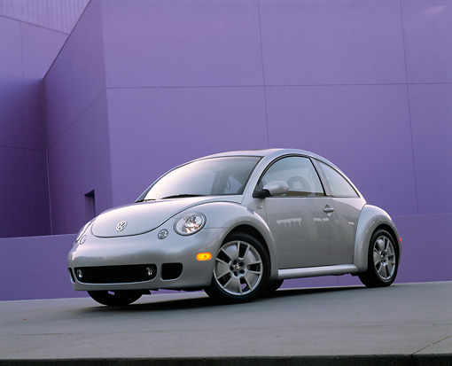 AUT 35 RK0173 04 © Kimball Stock 2002 Volkswagen New Beetle Turbo S Silver Slanted 3/4 Front View On Pavement Against Purple Wall
