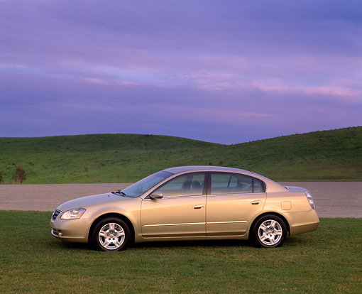 AUT 35 RK0188 01 © Kimball Stock 2002 Nissan Altima Champagne 3/4 Front View On Grass Cloudy