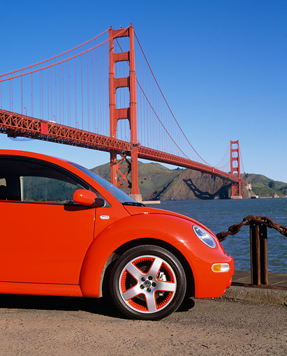AUT 35 RK0250 03 © Kimball Stock 2002 VW New Beetle GLS Turbo Orange Close Up By Golden Gate Bridge Blue Sky