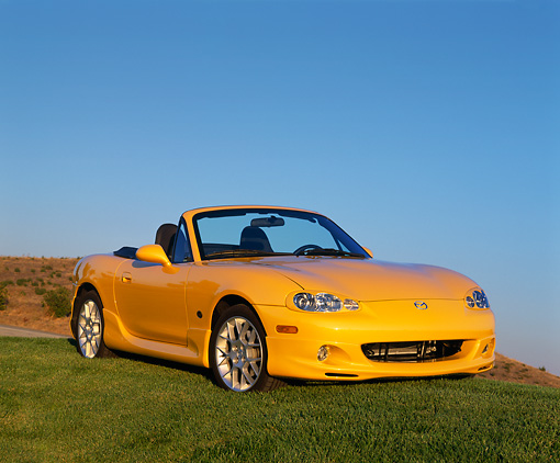 AUT 35 RK0256 04 © Kimball Stock 2002 Mazda Miata Special Edition Yellow 3/4 Front View On Grass Blue Sky