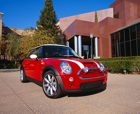 AUT 35 RK0292 01 © Kimball Stock 2002 Mini Cooper S Red With White Stripes Low 3/4 Front View On Pavement By Museum And Trees Blue Sky