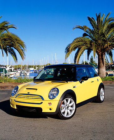 AUT 35 RK0302 01 © Kimball Stock 2002 Mini Cooper S Yellow And Black 3/4 Front View On Pavement By Harbor Blue Sky
