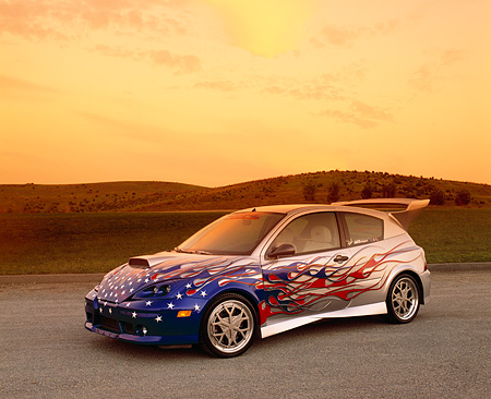 AUT 35 RK0328 05 © Kimball Stock 2002 Ford Focus FR200 Turbo Silver Patriotic Modify By APC 3/4 Front On Gravel Grass Hill In Fast & Furious 2