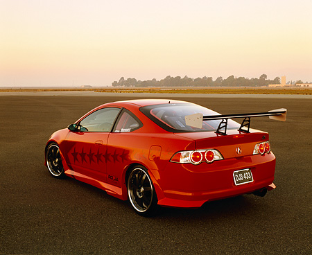 AUT 35 RK0341 02 © Kimball Stock 2002 Acura RSX Type S Red With Graphics Modify By APC Rear 3/4 View On Pavement At Dusk