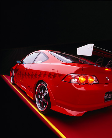 AUT 35 RK0343 12 © Kimball Stock 2002 Acura RSX Type S Red With Graphics Modify By APC Wide Angle 3/4 Rear Side View On Red Floor Studio