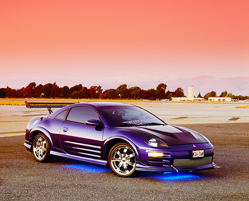 AUT 35 RK0384 01 © Kimball Stock 2002 Mitsubishi Eclipse Violet Blue 3/4 Side View On Bottom Light On Pavement