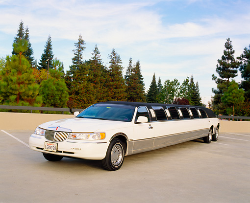 AUT 37 RK0003 09 © Kimball Stock 2000 Lincoln Town Car Stretched Limousine White 3/4 Front View On Pavement By Trees