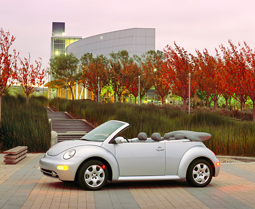 AUT 38 RK0085 02 © Kimball Stock 2003 VW New Beetle Convertible Silver 3/4 Side View On Pavement By Tall Grass And Stairs At Dusk