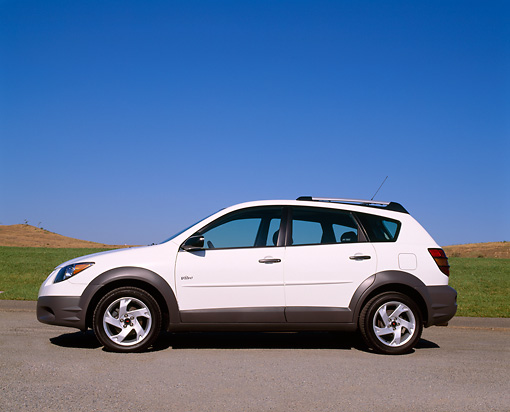 AUT 38 RK0016 08 © Kimball Stock 2003 Pontiac Vibe White Low Profile View On Pavement By Grass Blue Sky